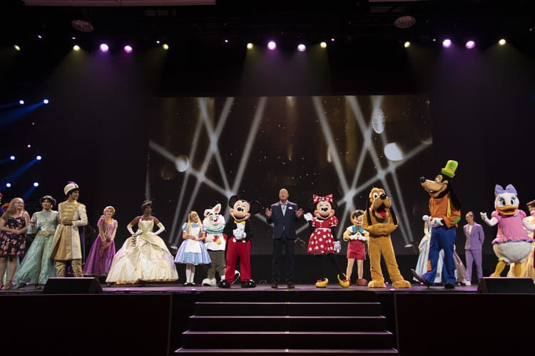 PRINCESS JASMINE, ALADDIN, RAPUNZEL, TIANA, ALICE, WHITE RABBIT, MICKEY MOUSE, BOB CHAPEK (CHAIRMAN OF PARKS, EXPERIENCES AND PRODUCTS), MINNIE MOUSE, PINOCCHIO, PLUTO, GOOFY, DAISY DUCK D23 Expo stage