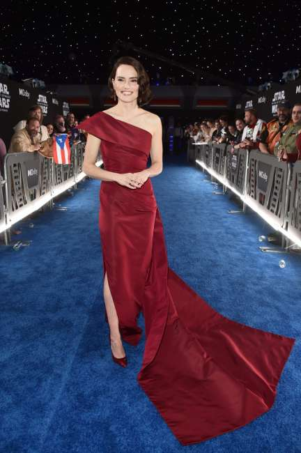 Daisy Ridley in a red dress on a blue carpet at the red carpet world premiere of Star Wars Rise of Skywalker